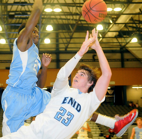 Enid's Braden Rogers collides with Lawton Eisenhower's Keyshawn Perkins as Rogers attempts a bucket at the Enid Event Center Saturday, Jan. 18, 2014. (Staff Photo by BONNIE VCULEK)