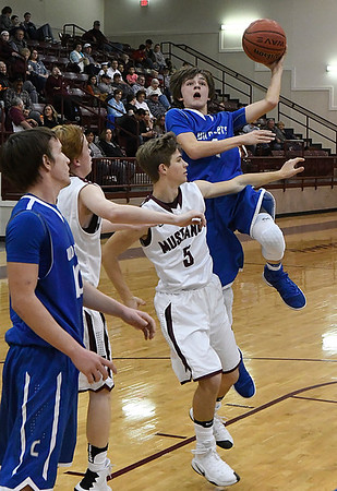 Covington-Douglas' Tate Vrska shoots over Pioneer's Dawson Maxwell Tuesday January 10, 2016 at Pioneer High School. (Billy Hefton / Enid News & Eagle)