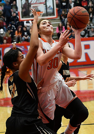 Fairview's Maddie Mason drives the lane for a shot against Woodward's Makale Floyd during the finals of the Wheat Capital Basketball Tournament Saturday January 7, 2017 at Chisholm High School. (Billy Hefton / Enid News & Eagle)