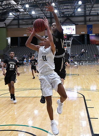 Enid's Darrin Ryan goes up for a shot against Midwest City's J.D. Ray Friday January 26, 2018 at the Central National Bank Center. (Billy Hefton / Enid News & Eagle)