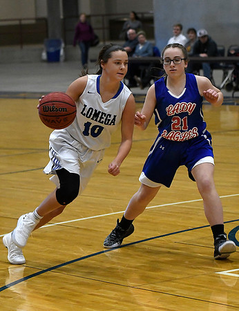 Lomega's McKenzi Lamer drives toward the basket against  DCLA's Abby Cardwell during the opening game of the Cherokee Strip Conference Basketball Tournament Thursday January 18, 2018 at the Chisholm Trail Expo Center. (Billy Hefton / Enid News & Eagle)