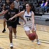 Enid's Elizabeth Plunkett drives by Putnam City North's Madison Callahan Tuesday January 30, 2018 at the Central National Bank Center. (Billy Hefton / Enid News & Eagle)