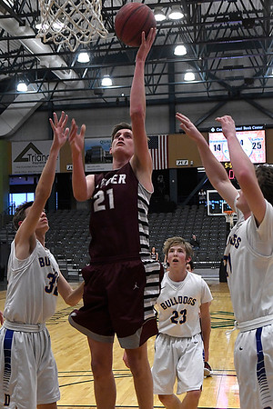 Garber's Jake Beebe scores in the middle of Drummond's Jake Isbell, Garrett Pool and Brandon Coontz Thursday January 18, 2018 during a semi final game of the 94th Annual Skeltur Conference Basketball Tournament at the Central National Bank Center. (Billy Hefton / Enid News & Eagle)