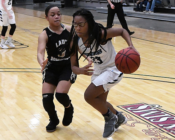 Enid's Jessica Emmerson drives towards the basket against Midwest City's Blesseth Dillingham Friday January 26, 2018 at the Central National Bank Center. (Billy Hefton / Enid News & Eagle)