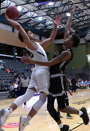 Enid's Cater Owens challenges Del City's Jeff Foreman at the basket Tuesday January 22, 2018 at the Central National Bank Center. (Billy Hefton / Enid News & Eagle)