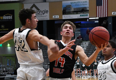 OBA's drives the lane against Thomas' Calen Fernandez during the Three Rivers Tournament Friday January 11, 2019 at the Central National Bank Center. (Billy Hefton / Enid News & Eagle)