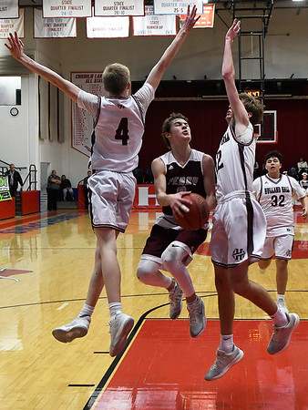 Perry's Jace Goldsberry jumps between Holland Hall's Kyle Hook and Mason Lee for a basket during the championship game of the Wheat Capital Tournament Saturday January 12, 2019 at Chisholm High School. (Billy Hefton / Enid News & Eagle)
