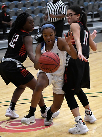 Enid's Bree Shaver drives towards the basket between Del City's Shawna Smith and Aliyah Dean Tuesday January 22, 2018 at the Central National Bank Center. (Billy Hefton / Enid News & Eagle)