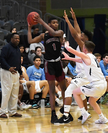 Enid's Will Phillips and Cory Simmons Jr. apply pressure to Putnam City North's Josh Nwankwo Tuesday january 29, 2019 at the Central national Bank Center. (Billy Hefton / Enid News & Eagle)