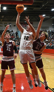 Kingfisher's Ian Daugherty scores against Perry's Noah Cash and Mason Drake during the finals of the Wheat Capital Basketball Tournament Saturday, January 11, 2020 at Chisholm High School. (Billy Hefton / Enid News & Eagle)
