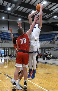 Cherokee's Treavor Green gets a hand in the face of Lomega's Noah Snowden during a semi-final gmae of the Cherokee Strip Conference Tournament Friday, January 22, 2021 at the Chisholm Trail Expo Center. (Billy Hefton / Enid News & Eagle)