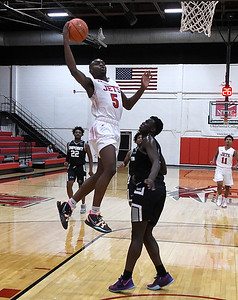 NOC Enid's Ikenna Okeke jumps pass On Point Academy's Abou Wage for a score Friday, January 22, 2021 Center at the NOC Mabee Center. (Billy Hefton / Enid News & Eagle)