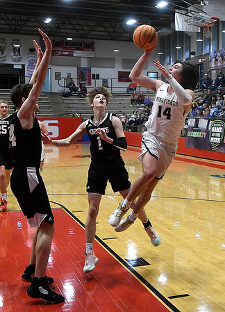 Kingfisher's Bijan Cortes puts up an off balance shot against OKC Knights' Josh Stephens and Connor Swanson during the championship game of the Wheat Capital Tournament Saturday, January 9, 2021 at Chisholm High School. (Billy Hefton / Endi News & Eagle)