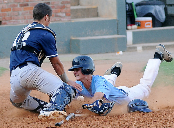 Enid Majors' Christian Voitik and OKC Drillers' Jake Johnson collide as Johnson dives and scores when the ball pops out of Voitik's glove at David Allen Memorial Ballpark Saturday, July 13, 2013. (Staff Photo by BONNIE VCULEK)