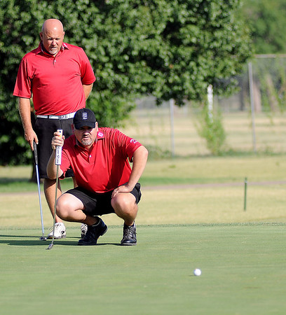 Jay Betchan and Darrin Busch align their putt on the No. 9 green as they compete in the Enid Ryder Cup with Josh Tobitt and Walker Hensen at Meadowlake Golf Course Friday, July 12, 2013. (Staff Photo by BONNIE VCULEK)