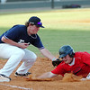 Woodward's Matt Martin dives into first as he is tagged by Enid's Garron Nixon on a pick off move Tuesday at david Allen Ballpark. Martin was called safe on the play. (Staff Photo by BILLY HEFTON)