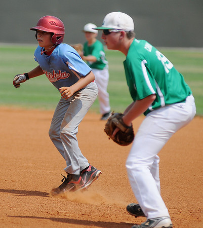 Chisholm's Logan McKee leads off first against Leedey RBI's Ashton Carman during the Red Dirt State Tournament at David Allen Memorial Ballpark Saturday, July 6, 2013. (Staff Photo by BONNIE VCULEK)