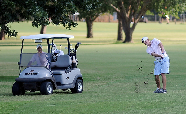 Walker Hensen watches as Josh Tobitt hits his approach on No. 9 as they compete during the Enid Ryder Cup at Meadowlake Golf Course Friday, July 12, 2013. (Staff Photo by BONNIE VCULEK)