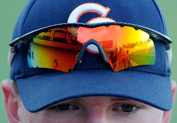 The sun's glow appears on the Oakley sunglass lens of a Cleveland County Boomer as temperatures remained in the upper 90s during the Enid Majors' game against the CC Boomers at David Allen Memorial Ballpark Friday, July 12, 2013. (Staff Photo by BONNIE VCULEK)