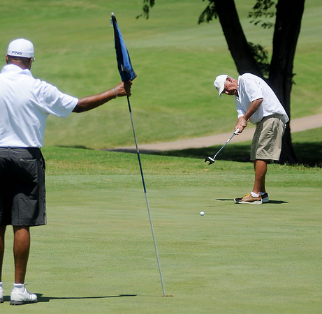 Jim Wetzel putts as Bob Lucky (left) holds the flag on No. 11 green during the Senior 4-ball tournament at Oakwood Country Club Monday, July 7, 2014. (Staff Photo by BONNIE VCULEK)