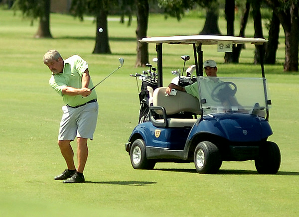 Oakwood Country Club's Jens Ruding hits his approach at the No. 9 green during the second round of the Enid Ryder Cup at Meadowlake Golf Course Saturday, July 26, 2014. The final round begins at 10;30 a.m. at Oakwood Country Club. (Staff Photo by BONNIE VCULEK)