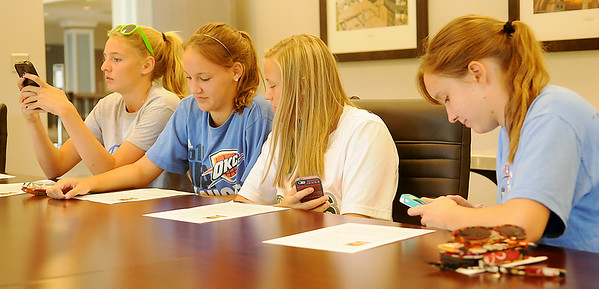Enid Pacers basketball players text other teammates as they read the press release on Jennifer Burch, their new head coach, during a press conference at Enid Event Center Tuesday, July 8, 2014. (Staff Photo by BONNIE VCULEK)
