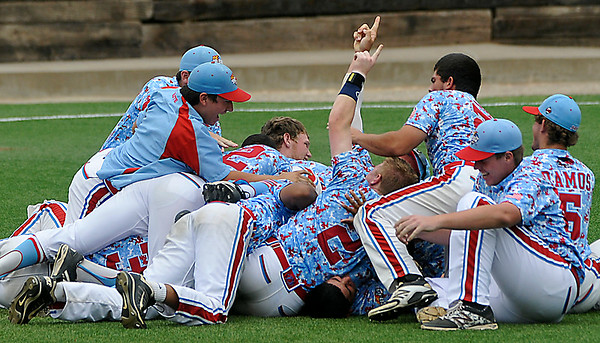 Members of the D-Bats Gallegos fall to the ground in a dog pile following the final out in the D-Bats 3-0 win over the Dallas Mustangs in the championship game of the Connie Mack regional tournament at David Allen Memorial Ballpark. (Staff Photo by BILLY HEFTON)