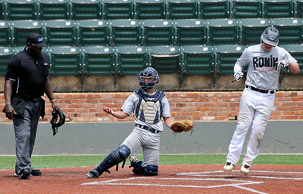 Enid's Christian Voitik gestures toward the dugout as Ronin's Keagan Harris scores the winning run on a bases loaded walk in the bottom of the eighth inning Wednesday during an elimnation game in the Connie Mack regional tournament at David Allen Memorial Ballpark. (Staff Photo by BILLY HEFTON)
