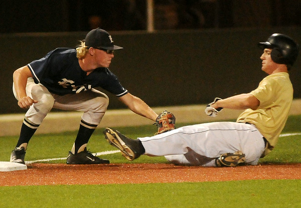 Enid Majors' Tanner Fore (left) tags an OKC Sandlot player out at third during the top of the first inning at David Allen Memorial Ballpark Friday, July 11, 2014. (Staff Photo by BONNIE VCULEK)
