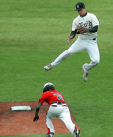 Enid's Brady Kokojan is caught in the air jumping for a high throw as Christian Rangel of the Oklahoma Racers dives into second Thursday during the Connie Mack state tournament Thursday at David Allen memorial Ballpark. (Staff Photo by BILLY HEFTON)
