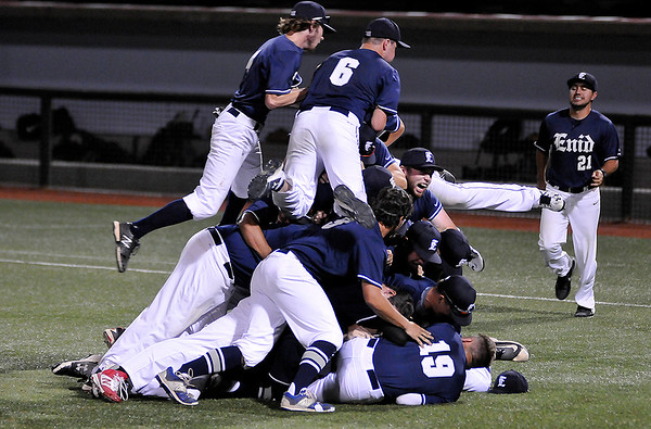The Enid Majors dog pile on the turf of David Allen Ballpark after defeating the Woodward 18s 6-4 to win the Connie Mack state championship Saturday July 16, 2016. (Billy Hefton / Enid News & Eagle)