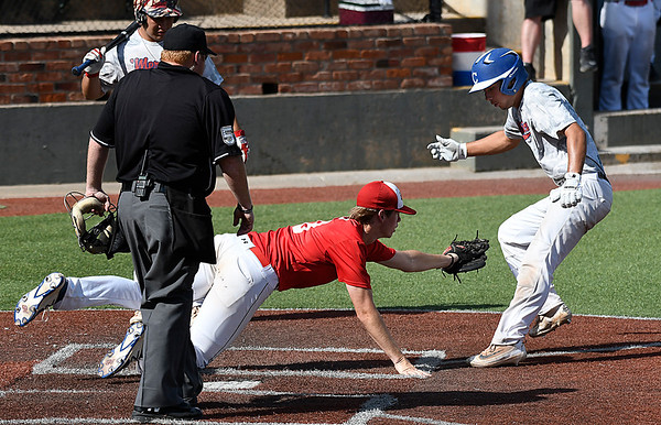Treston Shallenberger of the Albuquerque Cage Rats tries to avoid the tag of Oklahoma Expo's Michael Taylor during an elimination game in the Connie Mack Regional Tournament Friday July 21, 2017 at David Allen Memorial Ballpark. (Billy Hefton / Enid News & Eagle)