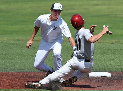 Austin Kuhlman of the SW Shockers Red tries to avoid the tag of Enid Plainsmen's Connor Gore during the opening day of the Connie Mack state tournament Wednesday July 12, 2017 at David Allen Memorial Ballpark. (Billy Hefton / Enid News & Eagle)