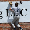 Enid Majors' Ryan Stotts runs into the outfield wall during the Connie Mack South Plains Regional Tournament game against NOLA Thursday July 19, 2018 at David Allen Memorial Ballpark. (Billy Hefton / Enid News & Eagle)