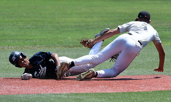 Enid Plainsmen's Willie Fleece dives into second pass Shockers Red's Rylee Holmes during the quarterfinals of the Connie Mack state tournament Saturday July 13, 2019 at David Allen Memorial Ballpark. (Billy Hefton / Enid News & Eagle)