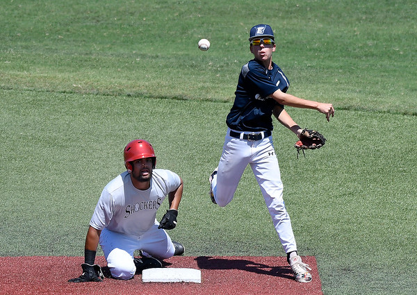 Enid Plainsmen's Kade Goeke throws to first after forcing out Shockers Red's Michelle Artsberger during the quarterfinals of the Connie Mack state tournament Saturday July 13, 2019 at David Allen Memorial Ballpark. (Billy Hefton / Enid News & Eagle)
