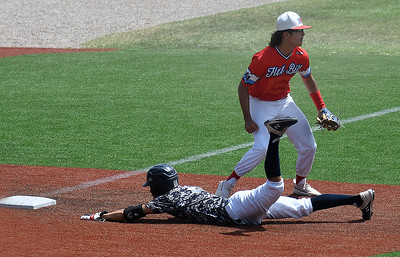 Enid Plainsmen's Maddux Mayberry dives into third base in fron of Flat Bill 17U's Julius Carpo during the Connie Mack South Plains Regional Tournament Wednesday July 8, 2020 at david Allen Memorial Ballpark. (Billy Hefton / Enid News & Eagle)