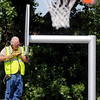 A gentleman installs new basketball hoops at Don Haskins Park Thursday, June 12, 2013. Give Me A Shot, a 501-C3 organization started by three Enid High School students, purchased the new goals and nets with donations. (Staff Photo by BONNIE VCULEK)
