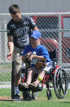 With a Miracle League buddy by his side, Dodgers' Dusty Decker hits a bunt at the AMBUCS ABC Park Saturday, June 1, 2013. The next league games will be this Thursday beginning at 6 p.m. (Staff Photo by BONNIE VCULEK)