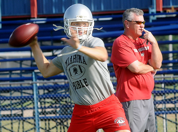 OBA's Preston Atwood looks for an open receiver as head coach, Mark Boyd, watches the play during Chisholm's 7-on-7 football camp at Longhorn Field Thursday, June 20, 2013. (Staff Photo by BONNIE VCULEK)