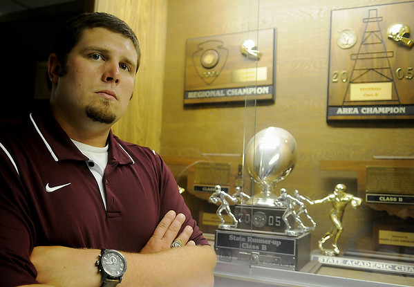 Gus Overstreet, Pioneer High School's new head football coach, pauses next to the OSSAA Class B State Runner-up trophy that he helped win in 2005. Overstreet, who coached at Covington-Douglas the past two years, returns to his alma matter to restore the Mustang's winning tradition. (Staff Photo by BONNIE VCULEK)