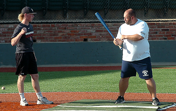 Enid coach, Chris Jenson, works with Tanner Fore during batting practice at David Allen Memorial Ballpark Tuesday. (Staff PHoto by BILLY HEFTON)