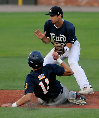 Enid's Brady Kokojan waits on the ball as Bartlesville's Ryan Behar slides into second attempting to steal. Behar over slid the base and was tagged out on the play. (Staff Photo by BILLY HEFTON)