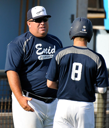 Enid Plainsmen coach, Brad Gore, coaches Connor Gore between innings Monday June 6, 2016 at David Allen Ballpark. (Billy Hefton / Enid News & Eagle)