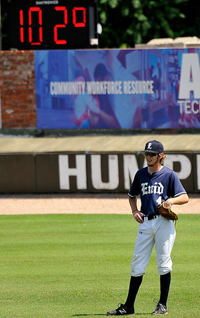 The ballpark temperature reads 102 degrees as Enid Majors' Bryan Ramey stands in right field between pitches Tuesday June 21, 2016 at David Allen Ballpark. (Billy Hefton / Enid News & Eagle)