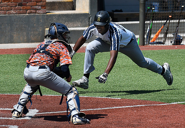 Enid Majors' E.J. Taylor starts his dive around Ft. Smith Sportsmen catcher, Jake Smith, to score Saturday June 24, 2017 at David Allen Memorial Ballpark. (Billy Hefton / Enid News & Eagle)