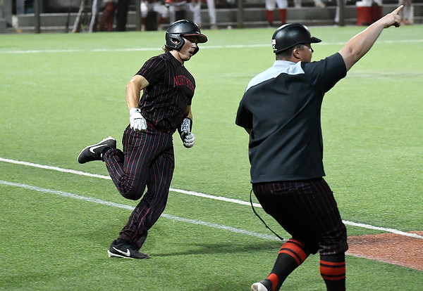 NOC Enid coach, Nolan Fanning, points to the outfield as Dylan Caplinger rounds the bases after hitting the game winning home run against Mesa CC to win the NJCAA DII national championship Friday, May 31, 2019, at David Allen Memorial Ballpark. (Billy Hefton / Enid News & Eagle)