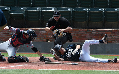 Enid Plainsmen's Maddux Mayberry rolls across home plate to score ahead of the tag from Catalyst Cardinals' Arz Fierer Thursday, June 13, 2019, during the Connie Mack Regional qualifying tournament at David Allen Memorial Ballpark. (Billy Hefton / Enid News & Eagle)