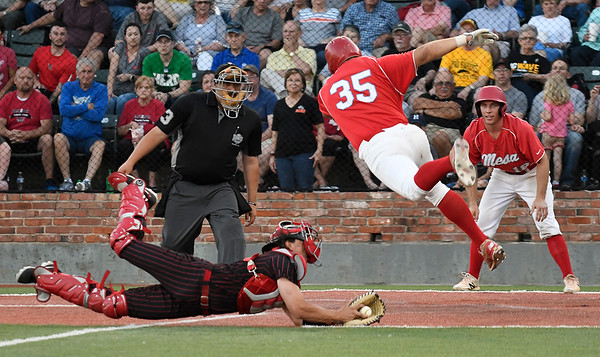 Mesa CC's Ben Ferguson leaps over the tag from NOC Enid's Dylan Caplinger to score during the NJCAA DII World Series national championship game Friday, May 31, 2019, at David Allen Memorial Ballpark. (Billy Hefton / Enid News & Eagle)