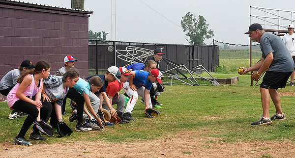 David Riesen works with campers on field stance during the Pioneer Baseball Camp Wednesday, June 9, 2021 at Pioneer High School. (Billy Hefton / Enid News & Eagle)